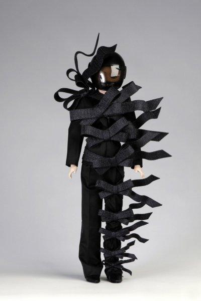 עיצוב, ויקטור ורולף. אדם במתנה. הבגד, כלומר האדם, מוחפץ וקשור בסרטים. גם הדוגמנית חבשה קסדה.