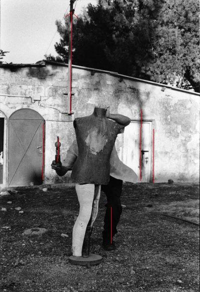 דניס סילק, צילמה: אביגיל שימל. זאת תמונה של ריקוד בשבילי, של תנופה והרמוניה לא צפויה. דניס החבוי הוא שמח מתגנב. חולצתו מתנופפת והקו האנכי של צינור החשמל הצמוד לבית כמו מקפיץ את השרביט למעלה וצל העץ (הנחבא בעצמו מאחורי הבית) מציץ כמין ראש חלופי.