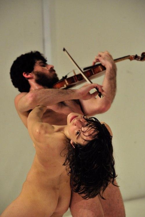 """מתוך """"שעה עם אוכלי כל"""", צילם מוריס קורבל (גרנות נתלית בזרועותיו של רומנו ומשבשת את הנגינה בכינור."""